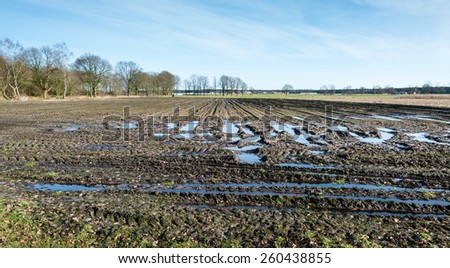 Muddy Belgian farmland with tire tracks in the foreground and the edge of a small village in the background on a sunny day in the end of the winter season. - stock photo