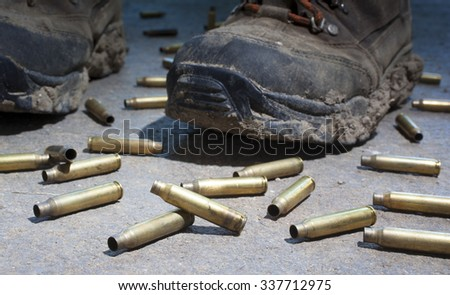 Muddy boots surrounded by rifle cartridges on concrete - stock photo