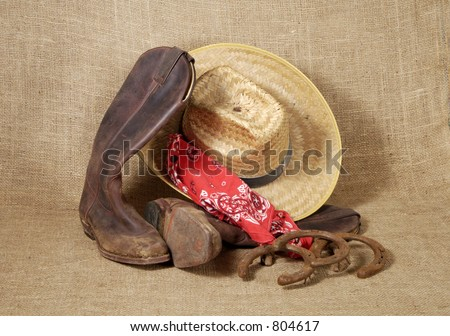 Muddy cowboy boots, straw hat , bandanna and old horseshoes on a burlap background. - stock photo
