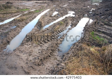 Muddy field with tire tracks and puddles - stock photo