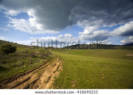 Muddy road in green spring field and blue sky with fluffy clouds- panoramic view - stock photo