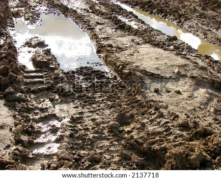 Muddy Road with bulldozer tracks in the mud and water puddle on a construction site - stock photo