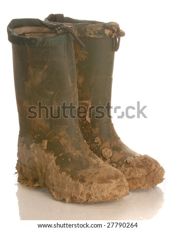 muddy rubber boots isolated on a white background - stock photo
