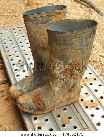 muddy rubber wellington gumboots - stock photo