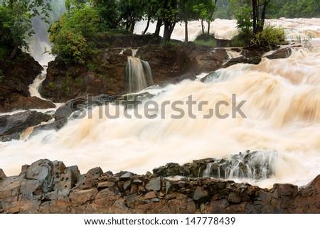Muddy waterfall with rain at Khone Phapheng Waterfall from Mekong River in Champasak Province, Laos - stock photo