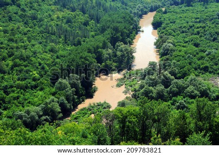 Muddy waters of the Yantra river in Bulgaria in the summer after heavy rains - stock photo