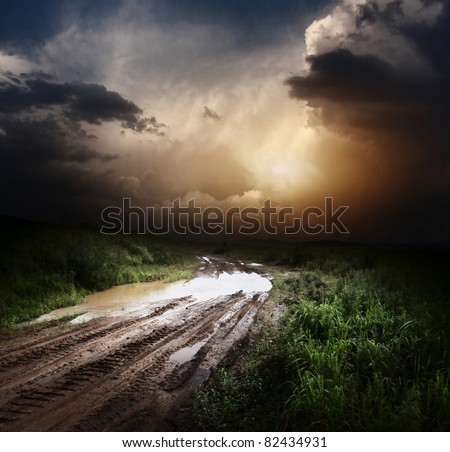 Muddy wet countryside road and dark storm clouds - stock photo