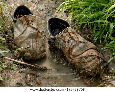 muddy worn out shoes in the puddle - stock photo