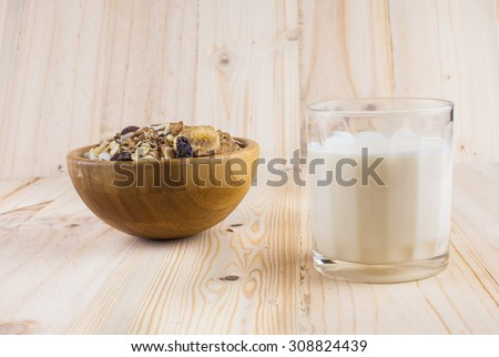 Muesli and a glass of milk on wooden table and background - stock photo