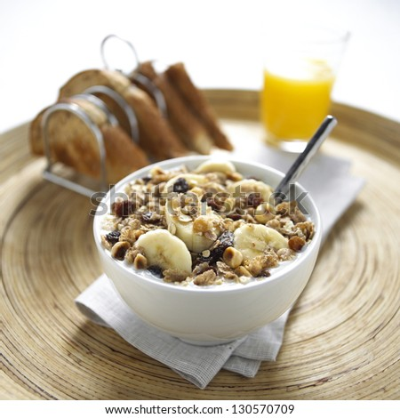 muesli banana breakfast in a bowl with toast in a rack and orange juice in a glass on a wooden tray - stock photo
