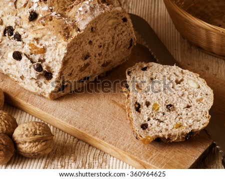 Muesli bread on plank with walnuts, knife and basket - stock photo
