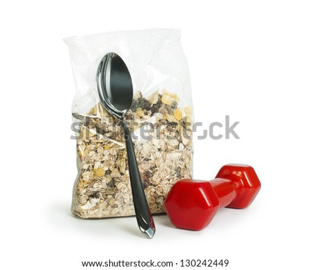 Muesli breakfast in transparent package.Spoon and dumbbell white isolated - stock photo