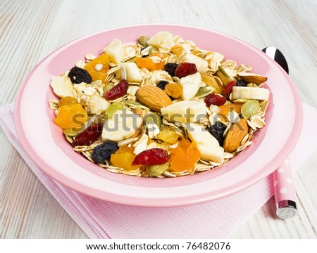 Muesli breakfast with dried fruit, almonds and slices of banana - stock photo