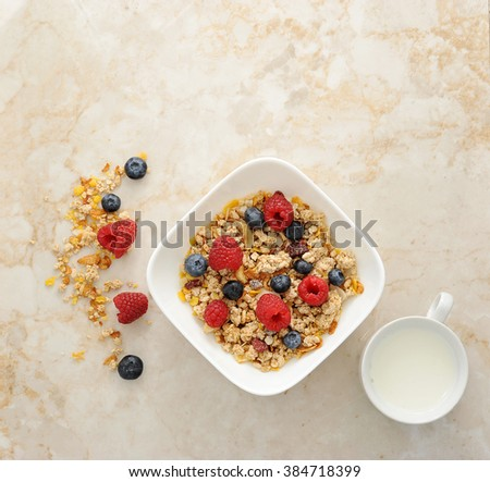 Muesli cereal with raspberries and blueberries. Mug of milk. Healthy food. Top view - stock photo