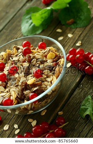 muesli in glass bowl and red currant on wooden boards
