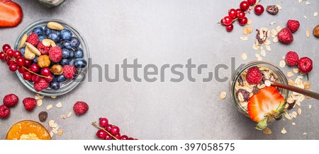 Muesli, nuts and berries. Breakfast preparation. Granola with fresh berries in jar on stone background, top view, banner.  Healthy food and Clean Eating concept - stock photo