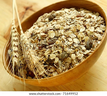 muesli of oats with raisin in wooden bowl - stock photo
