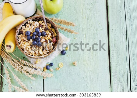 muesli with berries and fruit on a green wooden background. healthy breakfast - stock photo