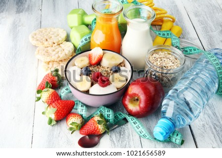 muesli with dairy and fruit, healthy lifestyle. bowl of cereal, fruit and dumbbell