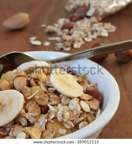 muesli with different nuts and banana on a brown wooden table