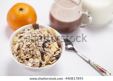 muesli with dried fruit chips in a white chinaware bowl with fresh orange coco and milk with a spoon at the side - stock photo