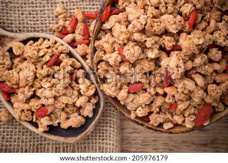 Muesli with goji berries in a bowl on a wooden background. - stock photo