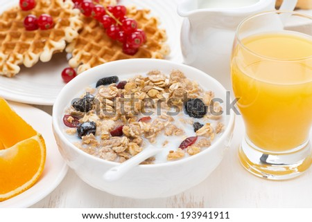 muesli with milk, sweet waffles and orange juice for breakfast, close-up - stock photo