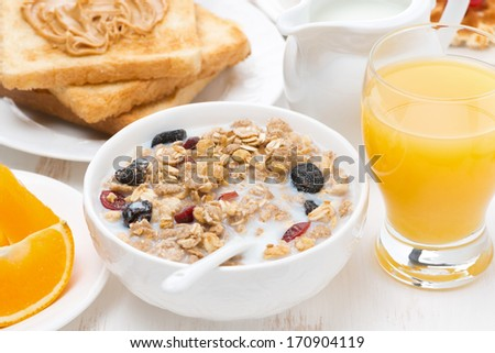 muesli with milk, toast with peanut butter and juice for breakfast, close-up - stock photo