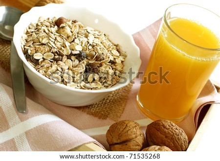 muesli with raisins in bowl, glass of orange juice - healthy breakfast - stock photo