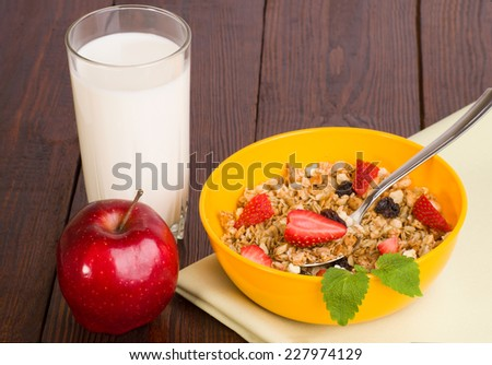 muesli with strawberries, apple and a glass of milk on a green napkin - stock photo