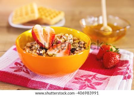 Muesli with strawberries served with honey - stock photo