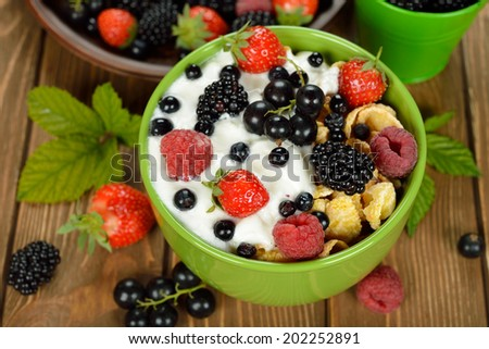 Muesli with yogurt and berries in a green bowl