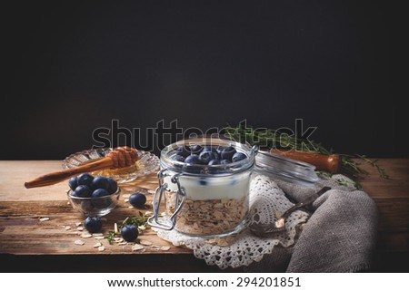 Muesli with yogurt and blue berries in glass jar on dark background. Healthy breakfast. Health and diet concept. Law key. Selective focus. - stock photo
