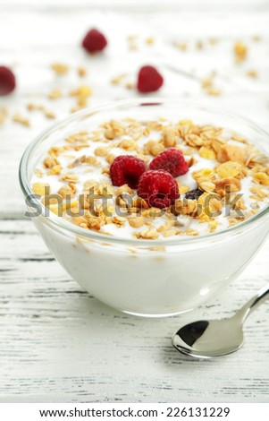Muesli with yogurt and raspberries in a bowl on a white wooden background - stock photo