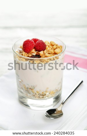 Muesli with yogurt and raspberries in a glass on a white wooden background - stock photo