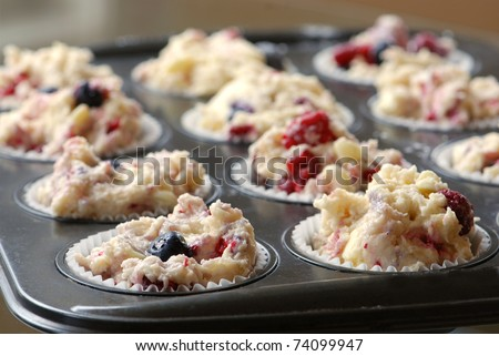 Muffin cups with dough ready for baking - stock photo