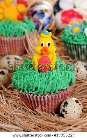Muffin decorated Easter chicken sitting on the grass