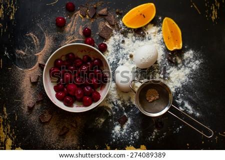 Muffin ingredients: the frozen cherry in a plate, orange segments, eggs, flour on a dark wooden background - stock photo
