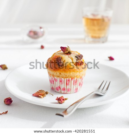 Muffin, mini cake, cup cake on a white plate with a rose buds tea on a white textile background - stock photo