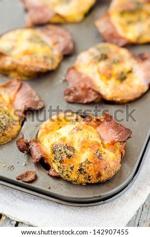 Muffin tin baked eggs with bacon mozzarella and Mediterranean spices - stock photo