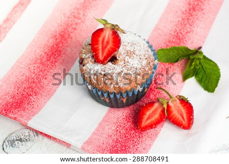Muffin with strawberries at the clothes - stock photo