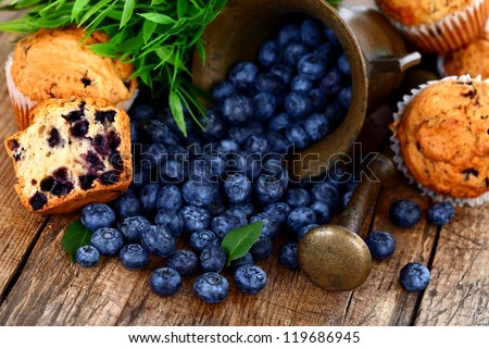 Muffins and blueberries on rustic wooden table - stock photo