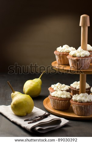 Muffins on a cake stand and peaches and vanilla - stock photo