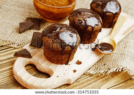Muffins with chocolate on a wooden table