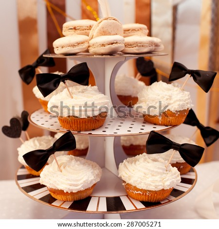 Muffins with cream on top, cup cakes, macaroons on plate. Birthday party decor. Celebration. - stock photo
