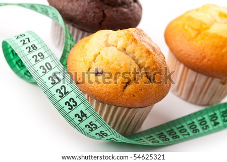 muffins with measuring tape on white background - stock photo