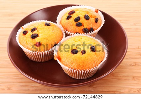 Muffins with raisins on wooden surface - stock photo