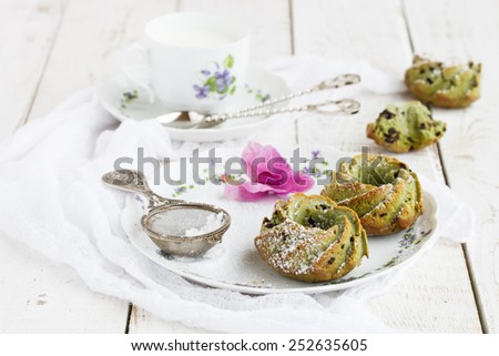 Muffins with tea match and chocolate ,sprinkled with powdered sugar