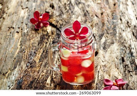 Mug delicious refreshing drink of mix fruits watermelon and cantaloupe on old wooden, infusioned water, soft focus  - stock photo
