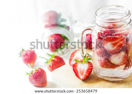 Mug delicious refreshing drink of strawberry on wooden, infused water - stock photo